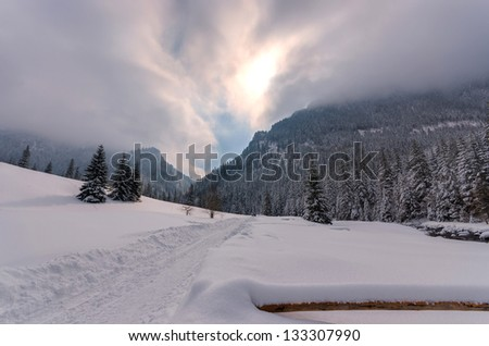 Winter landscape trail snow dramatic clouds sky sun, Koscieliska valley, Tatra Mountains