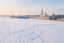 winter landscape, view of Hare Island and the Neva River covered with ice and white snow at sunset, famous tourist landmark historical fort fortress with the cathedral in St. Petersburg city, Russia