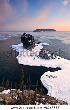 Winter landscape with a lone rock on the shore of the winter sea. Japan Sea.