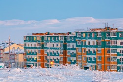 Winter landscape with a northern city in the Arctic. A view of the snow-covered tundra, colorful residential buildings and hills. Cold frosty February weather. Anadyr, Chukotka, Far North of Russia.