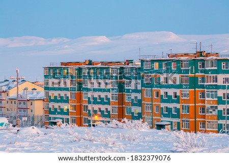 Photo of  Winter landscape with a northern city in the Arctic. A view of the snow-covered tundra, colorful residential buildings and hills. Cold frosty February weather. Anadyr, Chukotka, Far North of Russia.