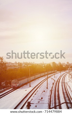 Winter landscape with a railway train on a railway surrounded by a city panorama with lots of houses and buildings against a cloudy sky background #714479884
