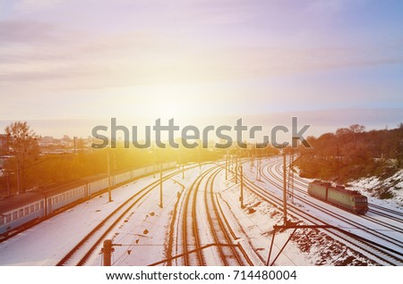 Winter landscape with a railway train on a railway surrounded by a city panorama with lots of houses and buildings against a cloudy sky background #714480004