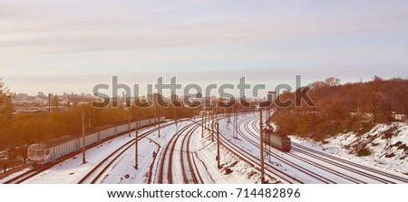 Winter landscape with a railway train on a railway surrounded by a city panorama with lots of houses and buildings against a cloudy sky background #714482896