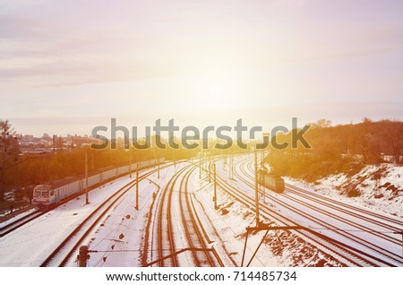 Winter landscape with a railway train on a railway surrounded by a city panorama with lots of houses and buildings against a cloudy sky background #714485734