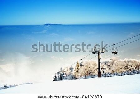 Winter landscape with a ski lift and ski slope - stock photo