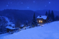 Winter landscape with a starry sky and mountain house with light in the window