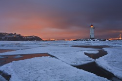 Winter landscape with a view of the lighthouse, iced sea and night city lights