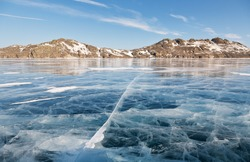 Winter landscape with blue ice with cracks on the frozen Siberian Lake Baikal