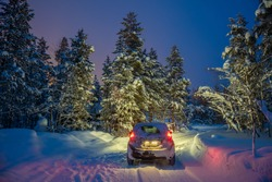Winter Landscape with car - Driving at night - Lights of car and winter snowy road in dark forest, big fir trees covered snow