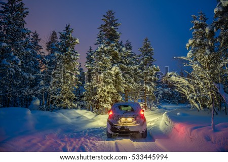 Stock Photo Winter Landscape with car - Driving at night - Lights of car and winter snowy road in dark forest, big fir trees covered snow