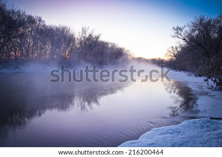 Winter landscape with foggy river at sunrise. Very cold weather.