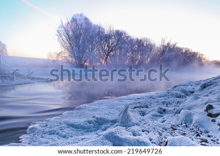 Winter landscape with frosty sunrise and winter river at very cold weather.