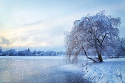 Winter landscape with lake and trees covered with frost with falling snow