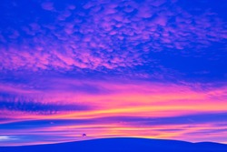 Winter landscape with mountain during amazing vivid saturated beautiful sunset sky in pink, purple and blue colors. Sunset background