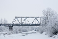 Winter landscape with railroad bridge over frozen river, snow-covered trees, hoarfrost.