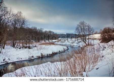 Winter landscape with river and snowy field