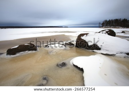 Winter landscape with rocks, lake and forest