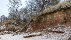 winter landscape with sandy beach, wild sea shore, red sand and clay outcrops on the sea shore, tree silhouettes on the shore, Vidzeme rocky sea shore, Tuja, Latvia