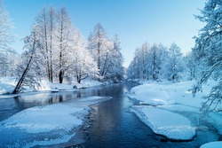 Winter landscape with small river in wood on background blue sky