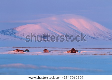 Photo of  Winter landscape with snow-covered houses and a mountain. Soft morning light. Abandoned cottages in the tundra. Cold May in the Arctic. Chukotka, Siberia, Far East of Russia.