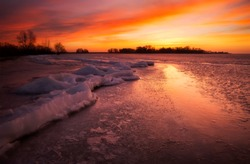 Winter landscape with sunset fiery sky.