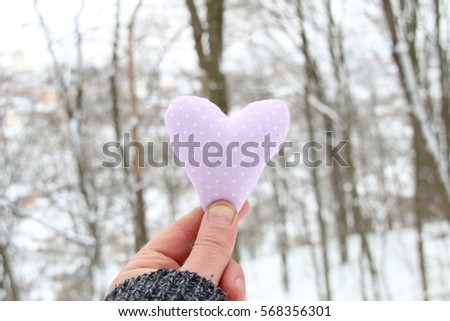 Winter, Love or Valentine's Day Concept. Hand holding a heart on the background of the  forest #568356301