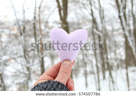Winter, Love or Valentine's Day Concept. Hand holding a heart on the background of the winter forest #574507786