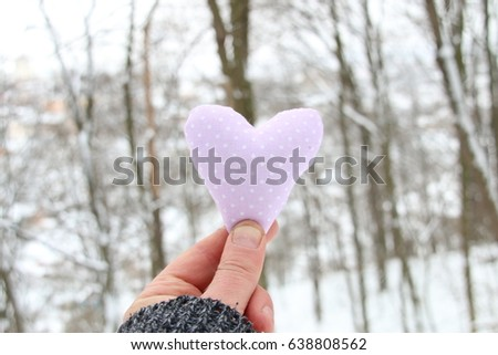 Winter, Love or Valentine's Day idea. Hand holding a heart on the background of the winter forest #638808562