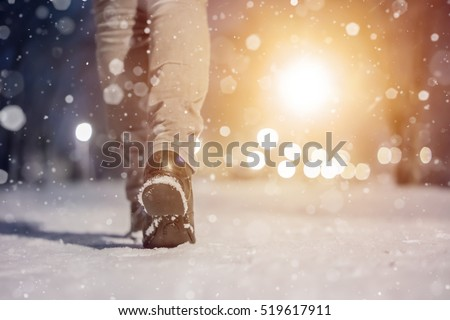 Winter macro photo of  woman boots. Girl walking in city park evening. Closeup photo of winter shoes. Blurred lens flare background with copy space area for a text. Snowfall in the wintry park.