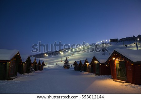 winter market village in Levi, Finland in the evenig on ski cable way background