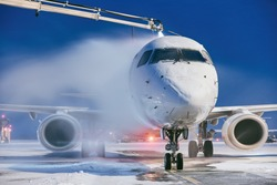 Winter morning at airport. Deicing of airplane before flight.