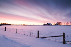 Winter morning landscape dramatic sky snow covered country field.