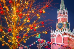 Winter Moscow. Chimes in capital of Russia. Kremlin on Christmas night. Tree with luminous garlands next to Kremlin tower. New Year's rest in Moscow. Russia on Christmas evening. Tour Russian cities.