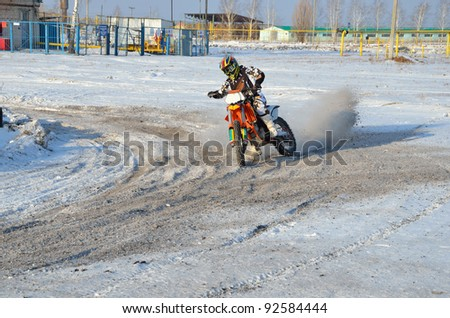 Winter motocross, the rider on motorcycle moves in a turnabout with the rear wheel skid on a snowy highway