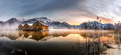Winter mountain lake panorama. Orange dawn nature panoramic landscape