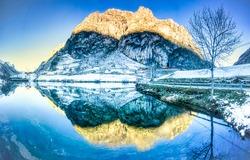 Winter mountain lake reflection view. Winter water reflection. Mountain winter snow reflectiob in water. Winter snow water reflection scene