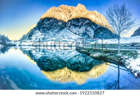 Winter mountain lake reflection view. Winter water reflection. Mountain winter snow reflectiob in water. Winter snow water reflection scene