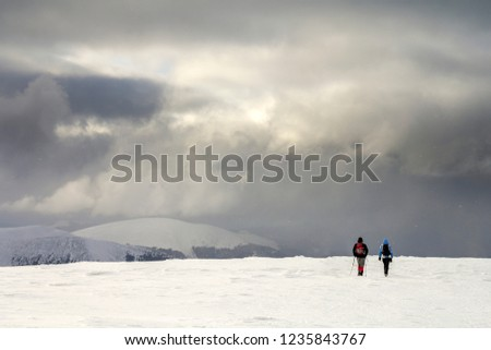 Winter mountain landscape. Back view of travelers tourist hikers with backpacks on snowy field walking towards distant mountain on cloudy dark blue stormy sky copy space background on cold winter day.