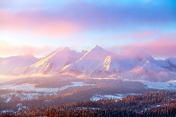 Winter mountain landscape. Mountain peaks covered by snow illuminated by rising sun. Pink clouds over mountains. Picturesque winter nature. Poland.