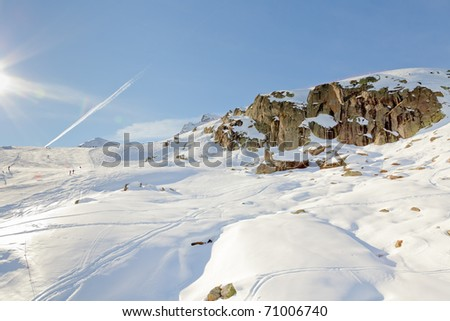 Winter mountain landscape with big rock under blue sky with sun rays. Alps. France.