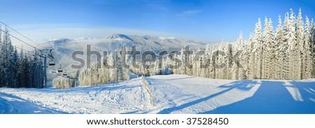 Winter mountain landscape with ski lift and skiing slope. Bukovel ski resort, Ukraine. Three shots stitch image.