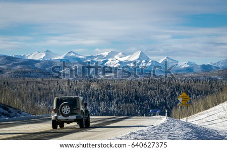 Winter mountain road with Rocky Mountains in a background, Alberta, Canada  #640627375