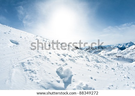 winter mountain scenery, fresh snow in foreground. cute mountain cabin buried in snow