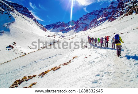 Winter mountain snow climbing team. Climbing team in mountain snow. Winter snow mountain climbing team. Mountain climb snow scene