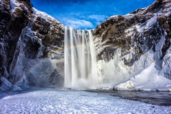 Winter mountain waterfall snow scene. Snowy mountain waterfall landscape. Winter mountain waterfall rainbow