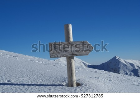 Winter mountains panorama with a wooden sign indicating the path. Abstract concept: the right way, the path, the direction.