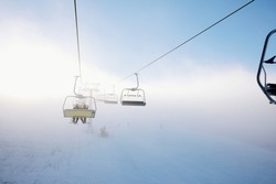Winter mountains panorama with ski slopes and ski lifts, sunny day with fog and sun rays