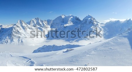 Stock Photo Winter mountains panoramic view with clouds in the valley and small hut. Corvatsch, Engadin, Switzerland.
