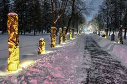 Winter night alley of chimeras with statues of monsters is covered with snow in the park of the city of Lutsk (Ukraine).